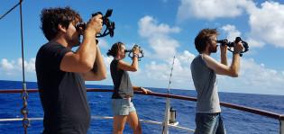 Kolme purjehdusoppilasta laivan kannella käyttämässä sekstanttia.