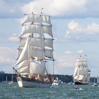 Suuri alus purjehtii purjeet ylhäällä. Takana pienempiä aluksia.