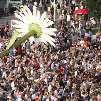 Laajakuva yleisöstä Tall Shio Races -tapahtumassa. Yleisö on kerääntynyt Forum Marinumin pihalla olevan Päivänkakkara-veistoksen ympärille.