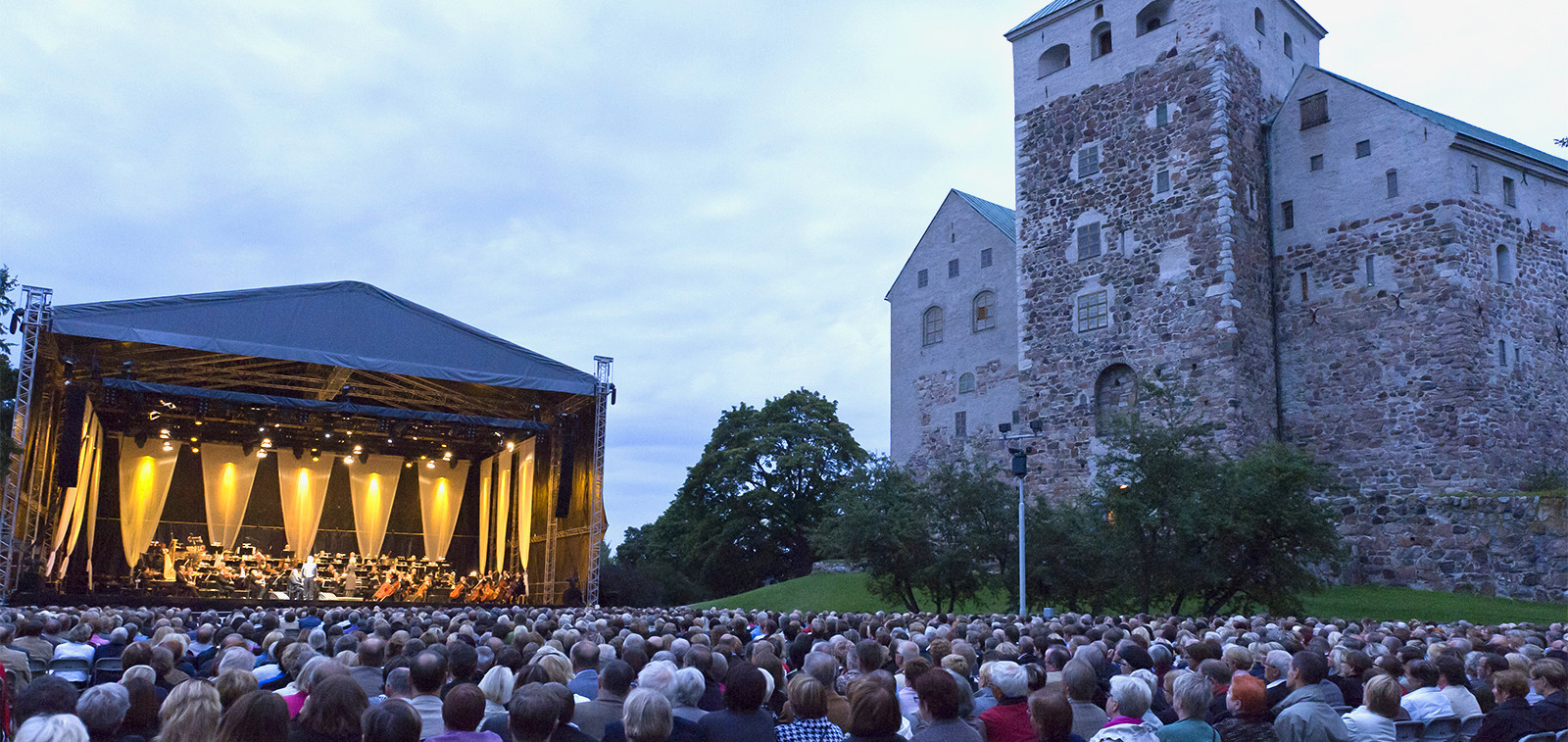 Konserttilava ja yleisöä Turun linnan edustalla Linnanpuistossa.